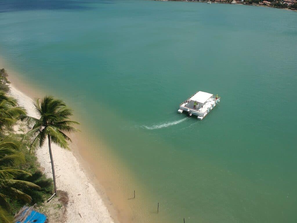 Imagem aérea de um catamarã passando na praia da restinga