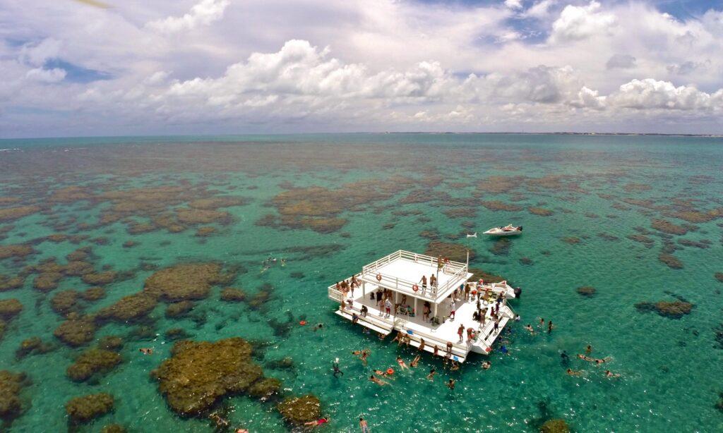Imagem aérea dos parrachos de maracajaú. Na imagem ao centro existe um catamarã com diversos turistas mergulhando em volta