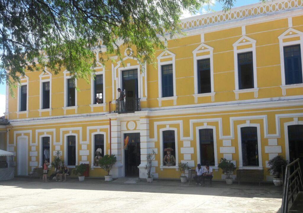 na imagem temos uma edificação amarela referente ao centro de turismo