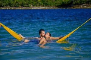 Na iamgem um casal dentro de uma rede na lagoa de Alcaçuz em nisia floresta