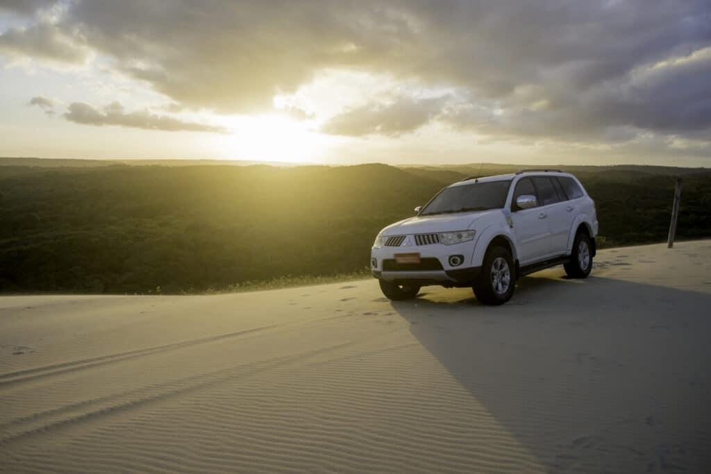 pajero branco em cima das dunas de malemba ao fundo da imagem o por do sol
